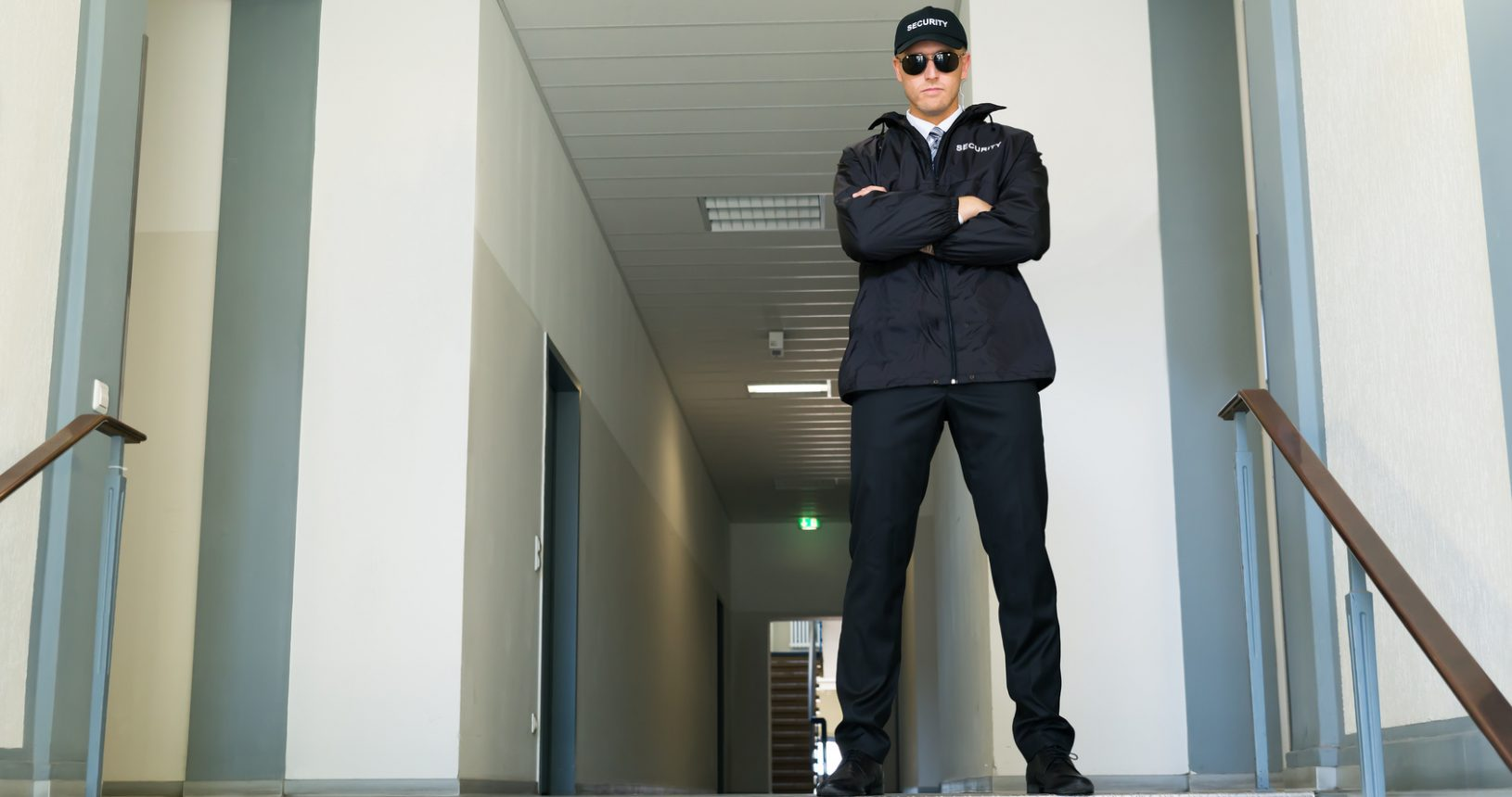 Male Security Guard Standing With Folded Arms At The Entrance